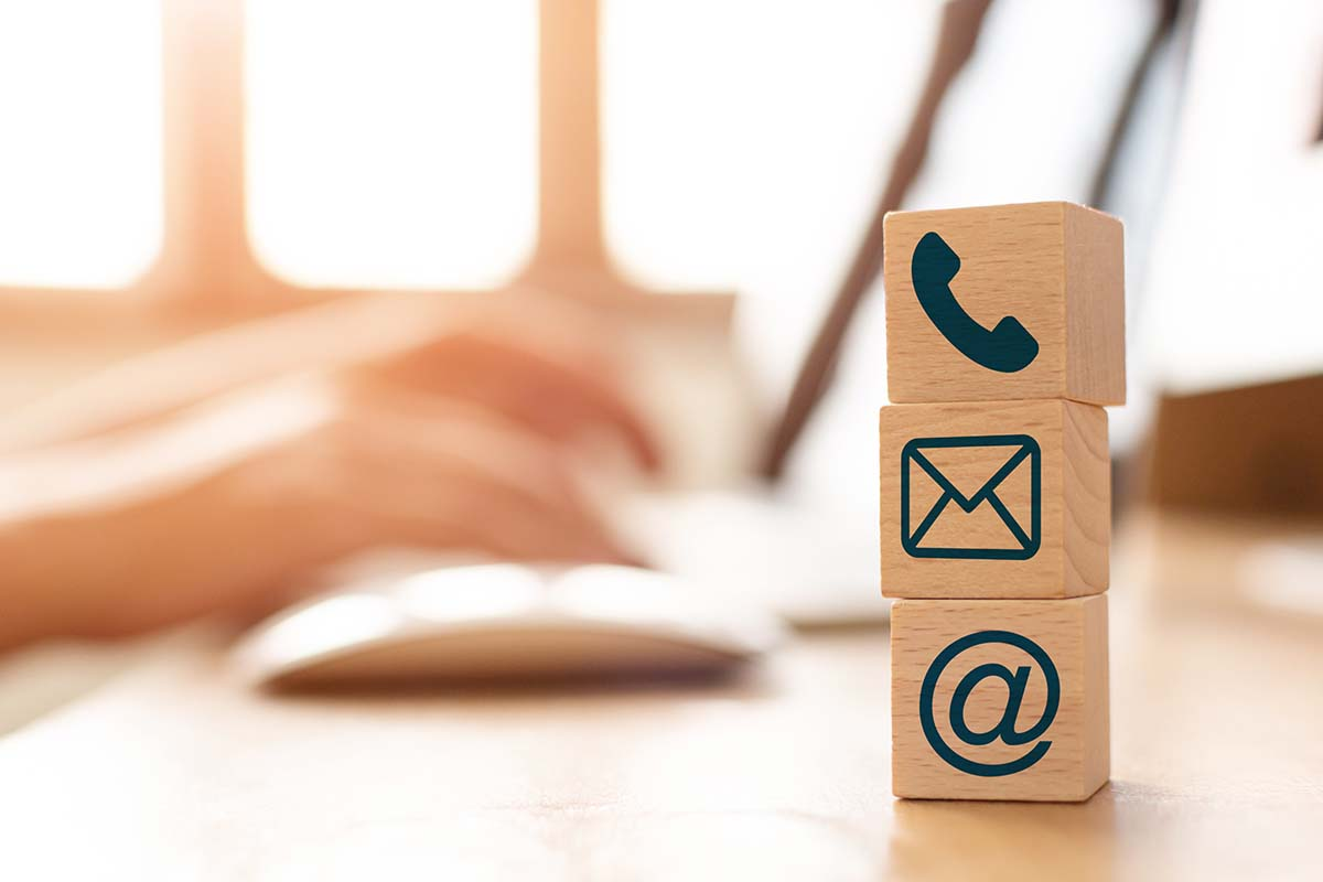 E-mail marketing concept, Hand using computer sending message with wooden cube block with icon mail address and telephone symbol